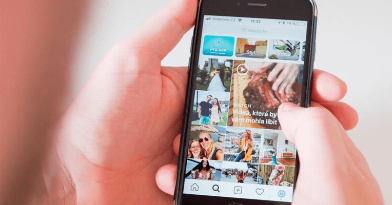 Hender holder en mobil og jobber med Instagram markedsføring