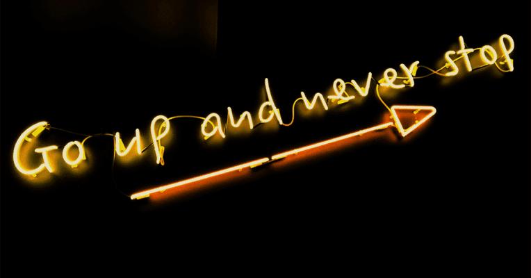 Gul neon tekst Go up and never stop på sort bakgrunn