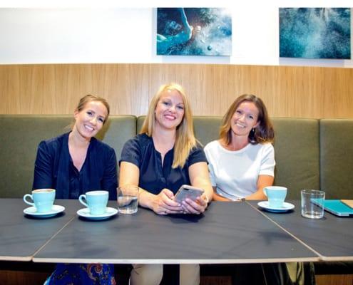 Tre smilende damer sittende ved et bord