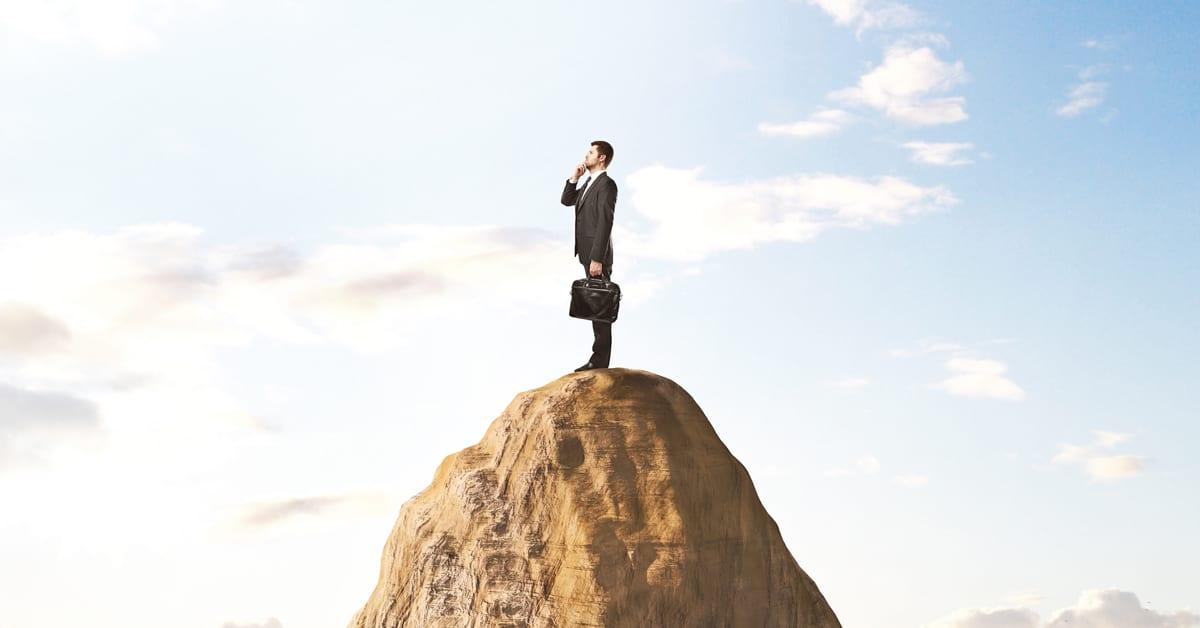 Mann i dress på toppen av et fjell