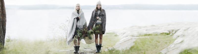 To damer bærer en en stråkurv fylt av blomster mellom seg