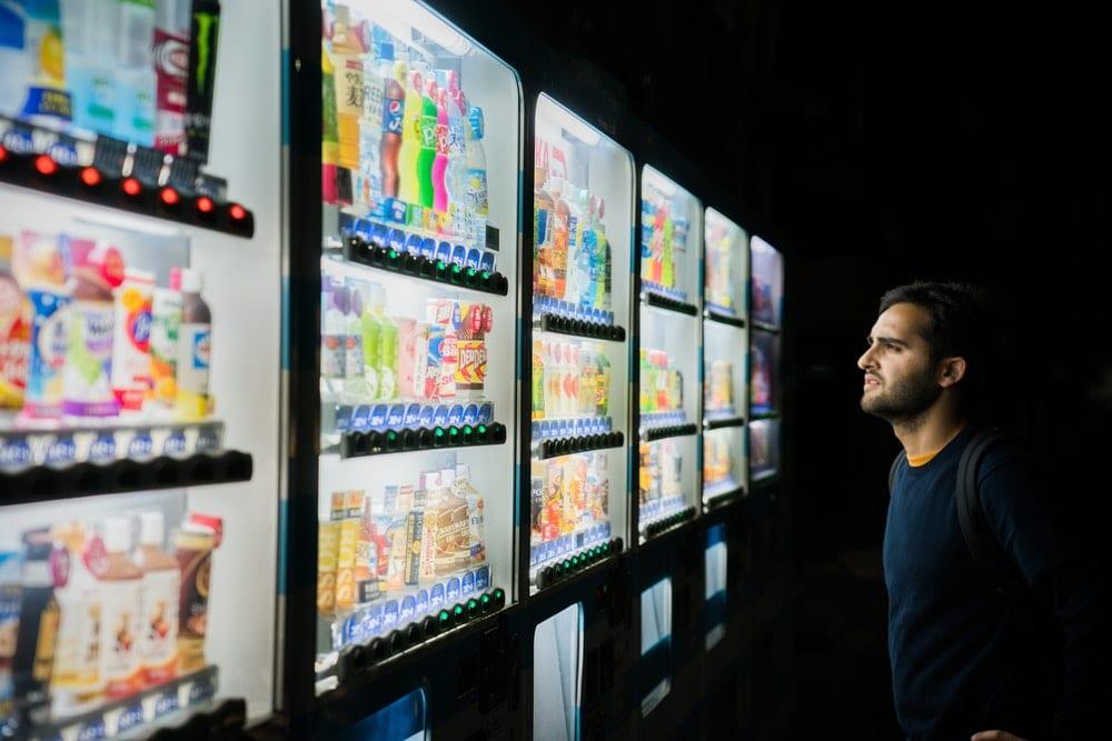 Mann ved brusautomat som velger mellom produktdesign