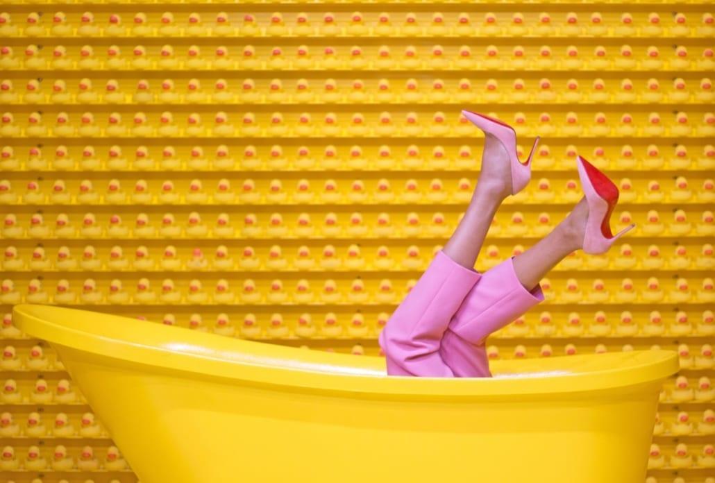 Fargerikt bilde av gult badekar, gul vegg og to føtter opp av badekaret med rosa bukse og sko