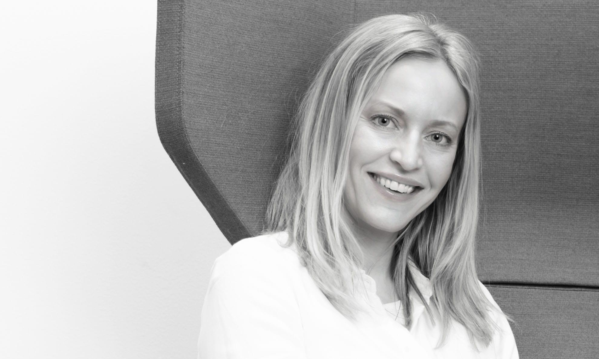 Tekstforfatter og PR-rådgiver Elin smilende i stol