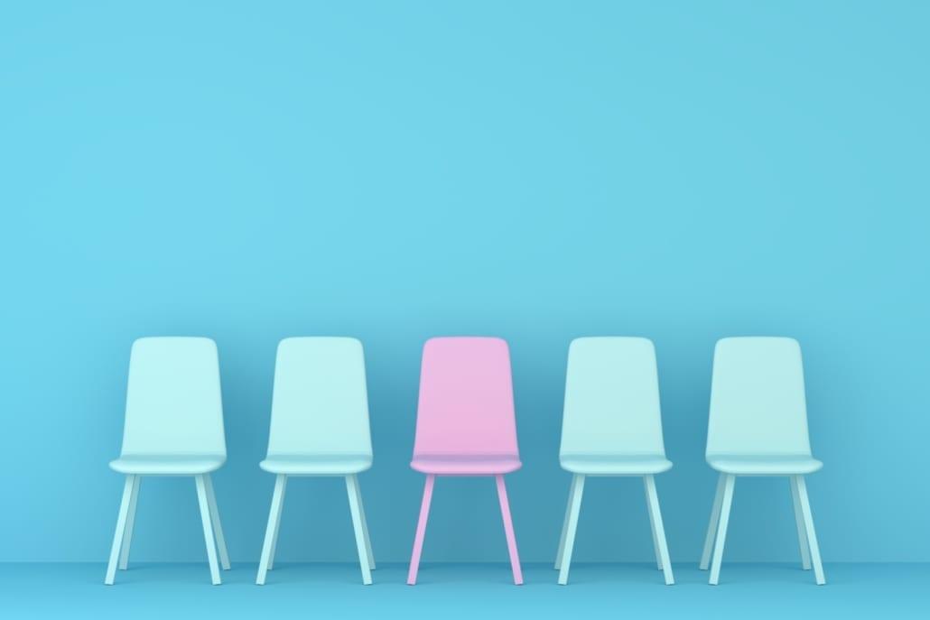 Blått rom med 4 blå stoler og en rosa stol i midten