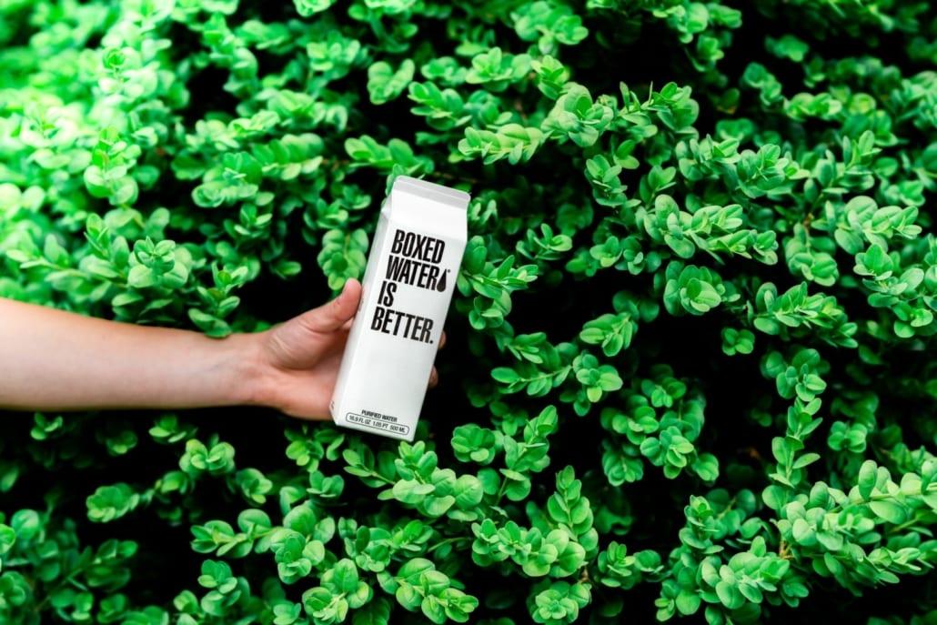 """Person som holder en kartong med teksten """"Boxed water is better"""""""