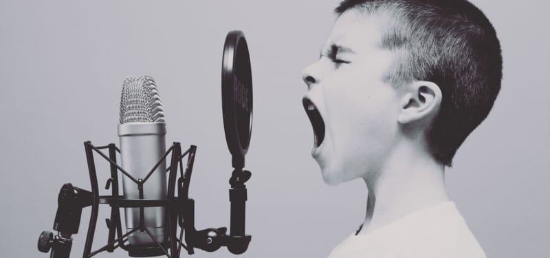 Gutt som skriker inn i mikrofon med filter