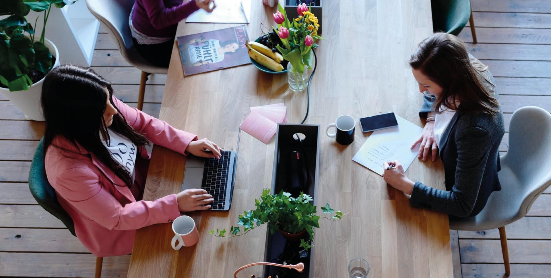 Damer sitter å jobber ved et bord