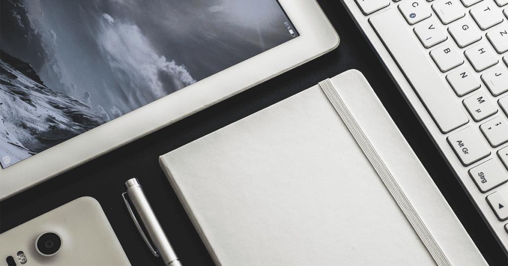 et nærbilde av et hvitt tastatur, mobil og nettbrett