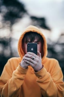 En gutt i gul hettegenser som holder en mobil foran ansiktet sitt