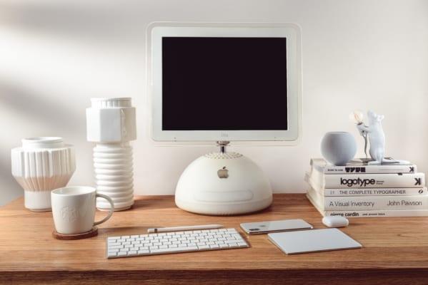 En pult med hvit mac og hvite kontorartikler rundt